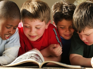 Four schoolboys reading